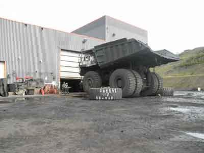 Un manipulador de neumáticos se acerca a un camión Komatsu 830E después que ingresa al centro de mantención de neumáticos en la mina Greenhills de Teck, cerca de Sparwood, B.C.