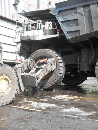 Después que el neumático viejo ha sido desmontado y que el conjunto de la rueda y el cubo han sido inspeccionados, un manipulador de neumáticos coloca un neumático nuevo en el 830E.