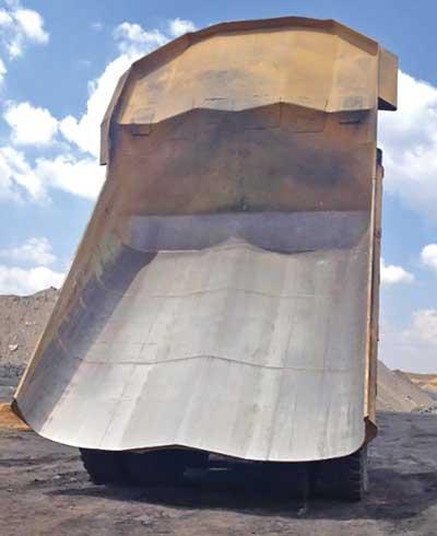 El diagrama de más arriba muestra la ruta del gas del escape en la cama de un camión calentada de VR Steel. La foto de abajo muestra los resultados del calentamiento de la cama del camión en una mina que anteriormente experimentó severos problemas de residuos de material.